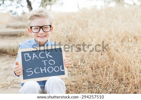 smart excited little boy in glasses holding chalkboard ready for school, back to school concept - stock photo
