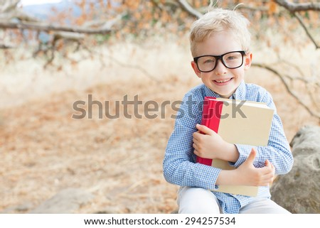 smart excited little boy in glasses studying with book ready for school, back to school concept