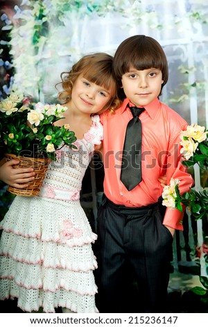 smart girl and boy with flowers in elegant clothes