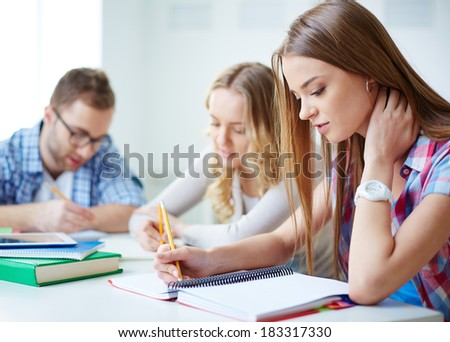 Smart girl carrying out written task with her groupmates on background - stock photo