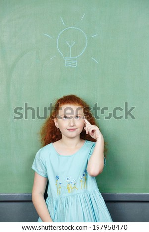 Smart girl has an idea with lightbulb over her head drawn on a chalkboard - stock photo