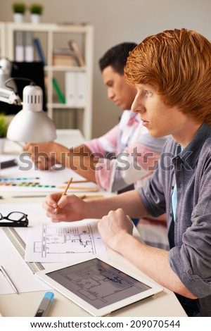 Smart guy thinking of construction sketch while sitting at workplace - stock photo