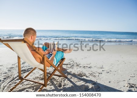 Smart handsome man reading a book on the beach - stock photo