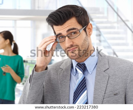 Smart handsome young caucasian bristly business expert with glasses at office. Confident, looking at camera, suit and tie. - stock photo