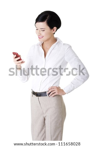 Smart happy young businesswoman using a smartphone - stock photo