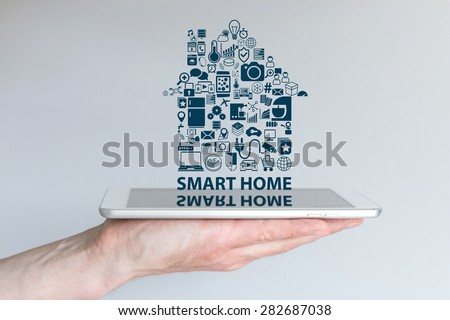 Smart home automation concept. Background with hand holding smart phone and floating text and icons. Reflections on screen. - stock photo