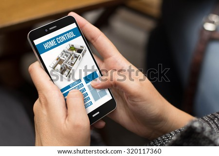 smart home concept: girl using a digital generated phone with home automation app on the screen. All screen graphics are made up. - stock photo