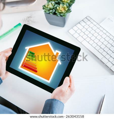 Smart home online energy efficiency rating chart displayed on the screen of a tablet held in the hands of a businessman sitting at his desk in the office - stock photo