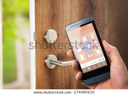 smart house, home automation, device with app icons. Man uses his smartphone with smarthome security app to unlock the door of his house. - stock photo
