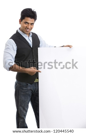 Smart Indian young businessman posing with white board - stock photo