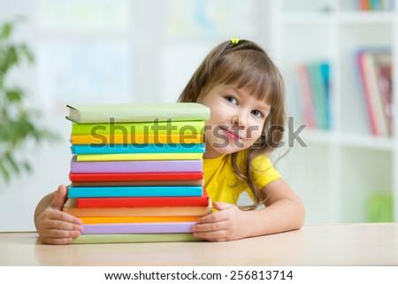 Smart kid girl preschooler with books in primary school - stock photo