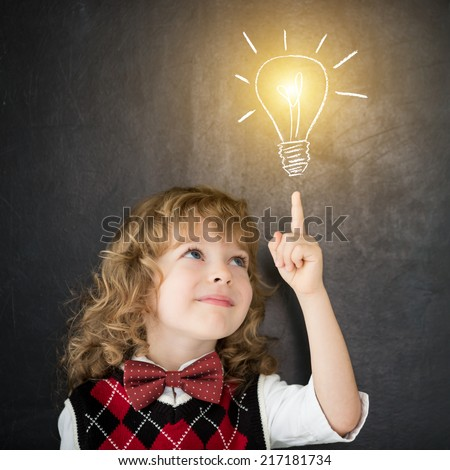 Smart kid in class. Happy child against blackboard. Drawing light bulb. Idea concept - stock photo