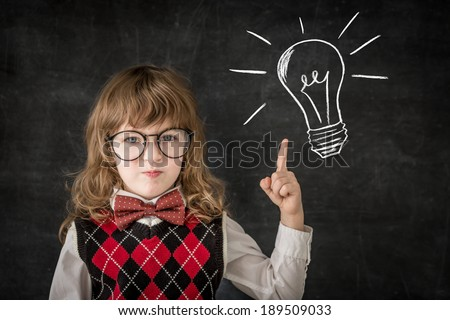 Smart kid in class. Happy child against blackboard. Education concept