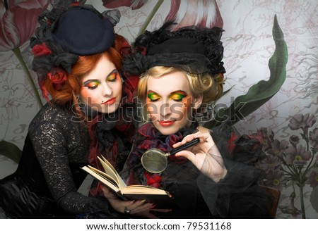 Smart ladies. Two young women in creative image with book and loop.