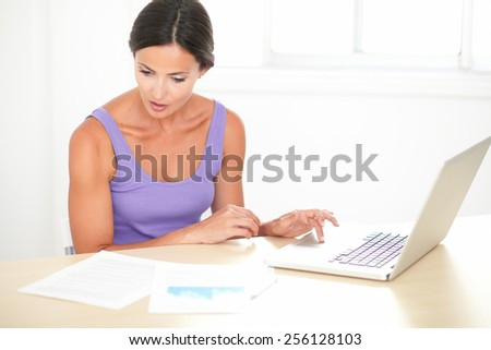 Smart latin woman in purple t-shirt studying on the computer at her home