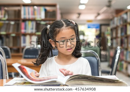 Smart little asian child girl w/ eyeglasses reading book school background: Lovely cute young female student kid opening flipping book in archive resource collection room: National library lover month - stock photo
