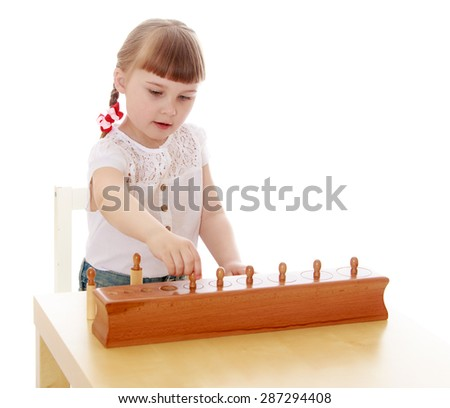 Smart little girl in a Montessori kindergarten sitting at the table playing with Montessori material-Isolated on white background - stock photo