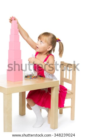 Smart little girl in Montessori kindergarten sitting at the table , and builds a pink pyramid - Isolated on white background - stock photo