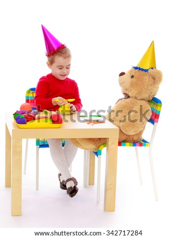 Smart little girl playing in a birthday party with a big Teddy bear . the head girl and Bear beautiful multi-colored party hats. - Isolated on white background