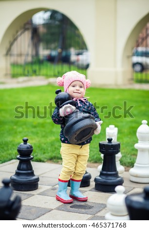 smart little girl taking a chessman while playing with giant chess outdoors