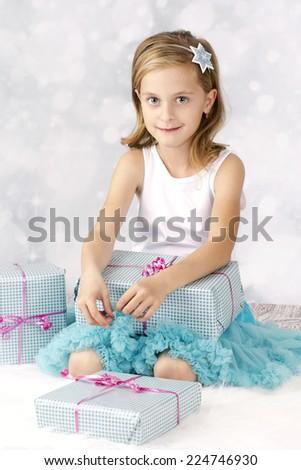 Smart little girl unpacking christmas presents - stock photo