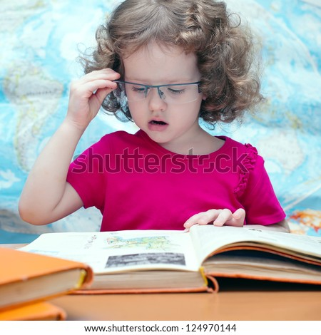 Smart little girl with glasses reading a book, square image - stock photo