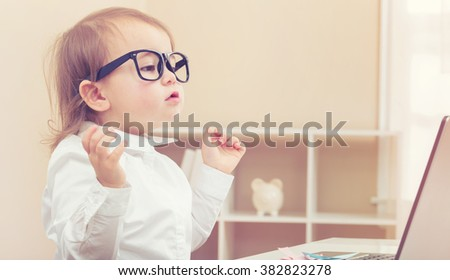 Smart little toddler girl wearing big glasses while using her laptop - stock photo