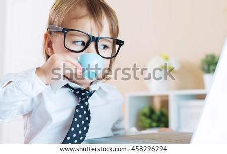 Smart little toddler girl with big glasses drinking coffee while using her laptop - stock photo