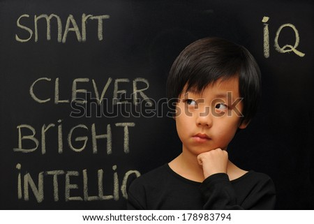Smart looking Asian boy against black background (blackboard with text) - stock photo