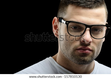 Smart looking guy with glasses in front of a black background
