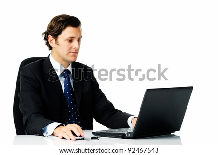 Smart looking man in a business suit works on his laptop computer, isolated on white - stock photo