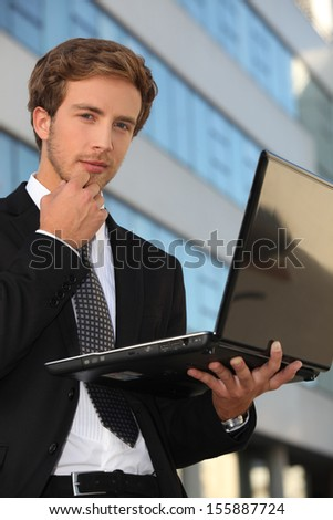 Smart man holding laptop standing outdoors - stock photo