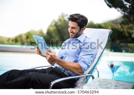 Smart man relaxing on sun lounger and using a digital tablet near the pool