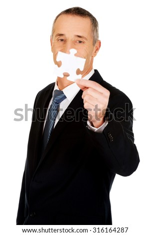 Smart mature businessman holding a puzzle