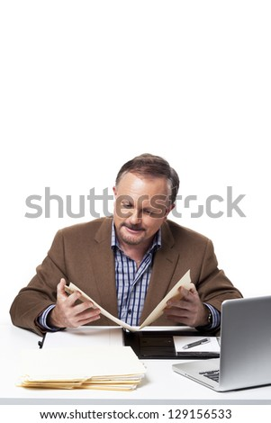 Smart mature businessman reading a file at work