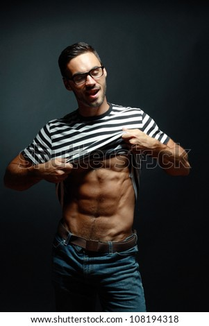 Smart muscular man in glasses, jeans and t-shirt  undressing over black background