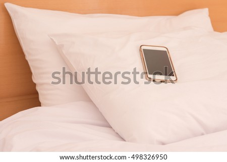 Smart phon laying on a white pillow in the bedroom
