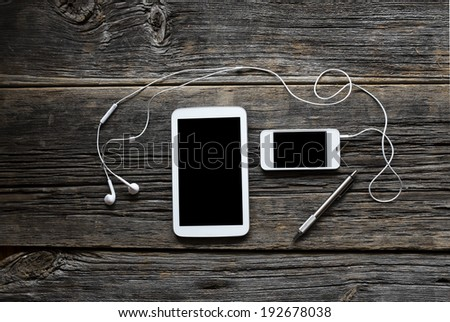 Smart-phone and computer tablet with pen and earbuds shot on rustic wood background - stock photo