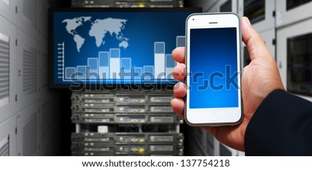 Smart phone and graph report in data center room - stock photo