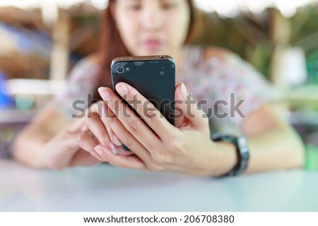 Smart Phone and lady's fingers on the screen - stock photo