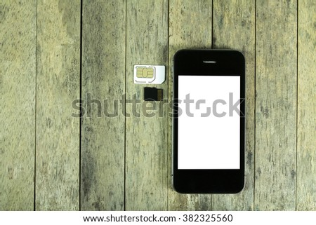smart phone and sim card, micro sd card on wood background - stock photo