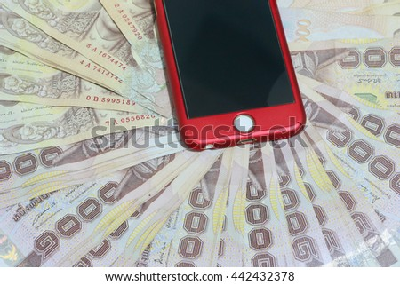 Smart phone and thai money on the white background - stock photo