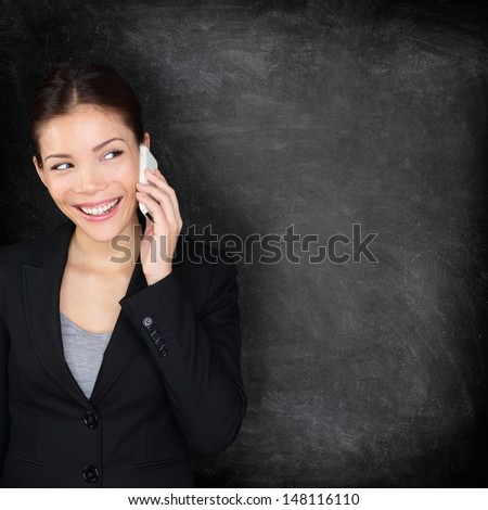 Smart phone blackboard, Woman on mobile phone looking at chalkboard sign showing copy space for your text or design. Business woman in suit talking smiling happy on smartphone, Asian Caucasian female. - stock photo