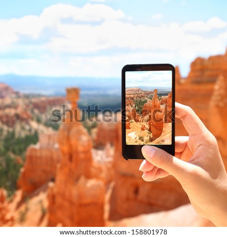 Smart phone camera taking photo picture of Bryce Canyon nature. Closeup of mobile phone camera screen photographing beautiful american landscape Bryce Canyon, Utah, United States. - stock photo