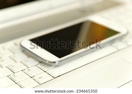 Smart phone close-up over laptop  - stock photo
