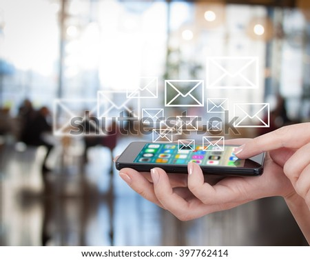 Smart phone emitting holographic image of social media related icons. Hand touching touch pad, social media concept. Blurred city background. - stock photo