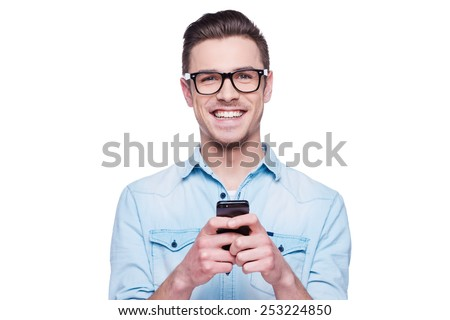 Smart phone for smart people! Handsome young man in shirt looking at camera and holding mobile phone while standing against white background  - stock photo