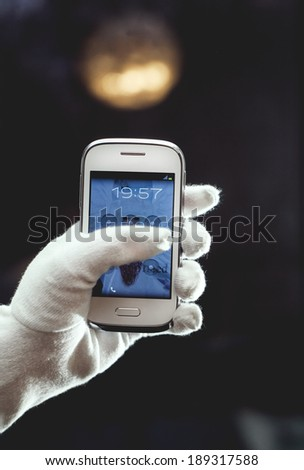 smart phone in hand, glove, blurred background - stock photo