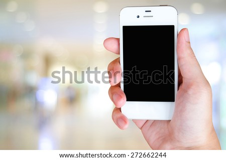 Smart phone in hand on blur store with bokeh background, business, technology concept