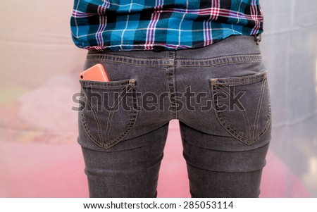 Smart phone in pocket of girl's jeans